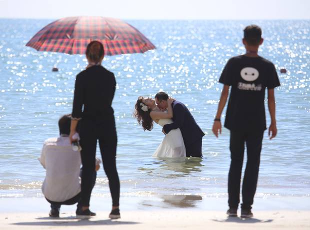 Couples pose for wedding pictures at Pleasant Banyan Bay in southern Guangdong, where rising seas have narrowed the beach by 10 metres.