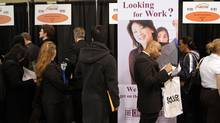 Job seekers line-up at various booths at a jobs fair in Toronto. (Fernando Morales/The Globe and Mail)