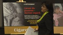 Health Minister Leona Aglukkaq walks past a new cigarette packaging image of lung cancer victim Barb Tarbox during a news conference in Ottawa on Thursday, Dec. 30, 2010. The government has introduced new cigarette packaging images to fight smoking among Canadians. (Pawel Dwulit/Pawel Dwulit/THE CANADIAN PRESS)