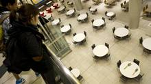 Shoppers peer down at flowers left on a table in the food court at the Eaton Centre in Toronto on Monday. While many teens were rattled, most also say they will be quick to return to the scene to reclaim their turf. (Kevin Van Paassen/The Globe and Mail)