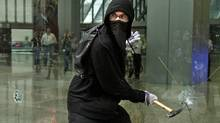 A violent anti-G20 protester uses a hammer to smash the windows of a downtown Toronto office tower on June 26, 2010. (Simon Hayter/Getty Images)