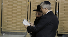 Canada's Prime Minister Stephen Harper looks at a Bible with Western Wall Rabbi Shmuel Rabinowitz as they stand in