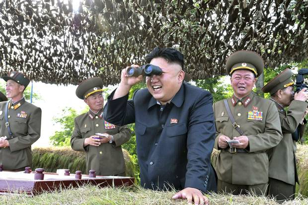 In an undated file photo, North Korean leader Kim Jong-un looks through a pair of binoculars during an inspection at a forward post off the east coast of the Korean peninsula.