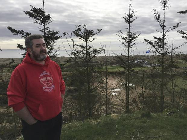 David Milne says the view from his home has been spoiled by the golf course and a 24-metre-high flag pole. His house was also surrounded by a fence and trees erected by the billionaire.