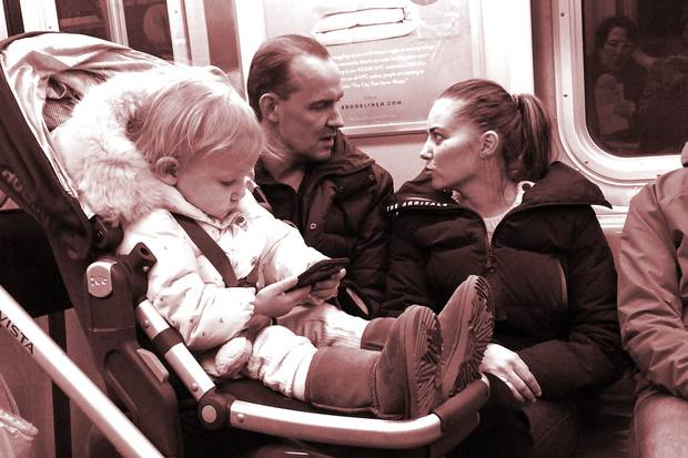 A baby plays with a mobile phone on a New York subway. Recent research posits a link between babies' smartphone use and how they develop eye contact with their parents, which can have an impact on brain development.