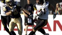 Hamilton Tiger-Cat Erik Harris, right, is chased by Winnipeg Blue Bombers receiver Brett Carter (Aaron Lynett/The Canadian Press)