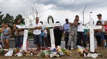 "People stand at a memorial for victims behind the theater where a gunman opened fire on moviegoers in Aurora, Colorado July 22, 2012. President Barack Obama travels to Colorado on Sunday to meet families bereaved after a ""demonic"" gunman went on a shooting rampage at a movie theater in a Denver suburb, killing at least 12 people and wounding 58. (Shannon Stapleton/Reuters)"