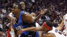 Orlando Magic centre Dwight Howard, left, is double teamed by Toronto Raptors forwards Chris Bosh and Antoine Wright during the second half of their NBA basketball game in Toronto November 1, 2009. Bosh drew a foul on the play. (MIKE CASSESE)