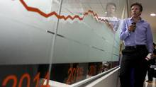 A foreign investor watches share prices during the opening ceremony at the Cambodia Securities Exchange in Phnom Penh April 18. (STRINGER/REUTERS)