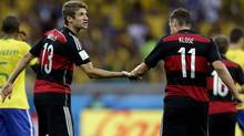 Germany's Thomas Mueller, left, is congratulated by teammate Miroslav Klose after scoring his side's first goal during the World Cup semifinal soccer match between Brazil and Germany at the Mineirao Stadium in Belo Horizonte, Brazil, Tuesday, July 8, 2014. (Associated Press)