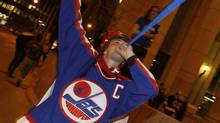 A hockey fan cheers at the corner of Portage and Main in downtown Winnipeg after media reports of the Atlanta Thrashers hockey team moving to Winnipeg, May 19, 2011. After years of false starts and false hope, hockey-obsessed Canada may finally reclaim its lost NHL team as speculation heated up this week that the league is set to return to Winnipeg 15 years after it left. REUTERS/Shaun Best (Shaun Best/Reuters)