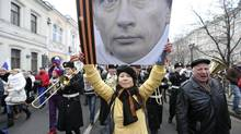 A woman holds a board displaying a portrait of Russian President Vladimir Putin during a procession in central Moscow, March 2, 2014. People gathered on Sunday to support the people of Crimea and Ukraine, and to protest against the policies conducted by Ukraine's new authorities recently elected in Kiev, according to organizers. (SERGEI KARPUKHIN/REUTERS)