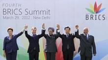 Brazil's President Dilma Rousseff, Russian President Dmitry Medvedev, Indian Prime Minister Manmohan Singh, Chinese President Hu Jintao and South African President Jacob Zuma join their hands together during a group photo for the BRICS Summit of emerging market nations in New Delhi March 29, 2012. (B MATHUR/REUTERS)