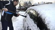 Emilio Deagazio woke up to find his car, parked on Toronto's Belcourt Rd., covered in snow and ice on Jan. 6, 2014. Freezing rain fell over Toronto overnight leaving sidewalks and roads covered in slush and ice. (Fred Lum/The Globe and Mail)