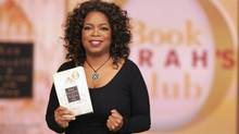 "Oprah Winfrey holding a book club selection, Ken Follett's ""The Pillars of the Earth,"" in 2007. (George Burns/AP)"