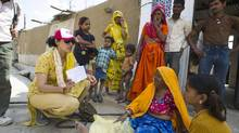 Chhavi Rajawat (left, in baseball cap) meets with some of her constituents in the village of Soda, near Jaipur, Rajasthan, India. (Simon de Trey-White)