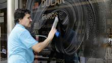 A worker cleans the window of a currency exchange billboard showing the official rates of foreign currencies to Argentine pesos in Buenos Aires January 27, 2014. (ENRIQUE MARCARIAN/REUTERS)