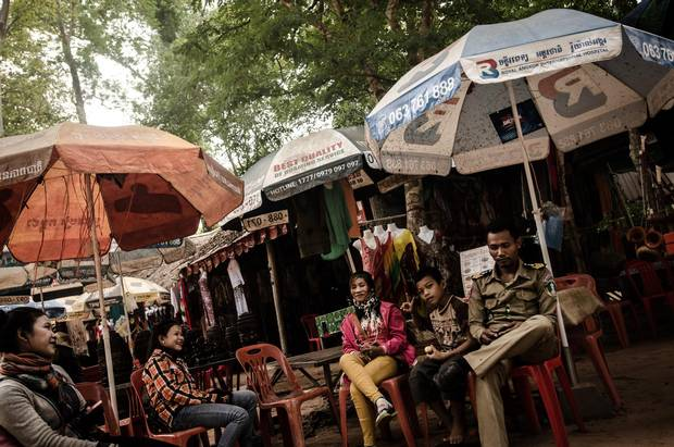 Local stall owners and a tourist police officer shade from the intense heat in an area close to where the dead body of 58-year-old Canadian writer and filmmaker Dave Walker was found.