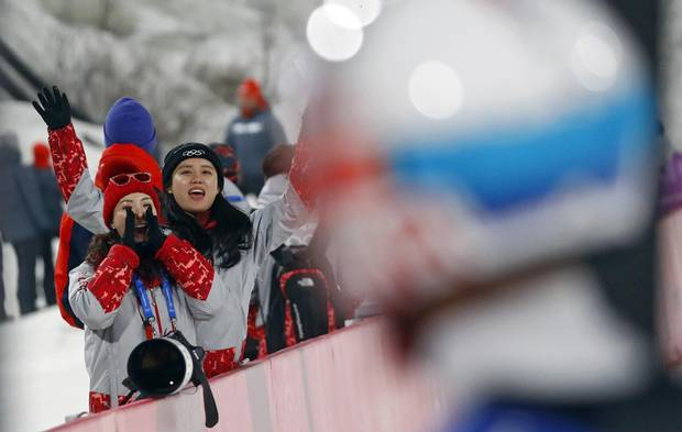 Volunteers cheer for South Korean ski jumper Choi Seou at the Alpensia Ski Jumping Centre in Pyeongchang on Feb. 19, 2018.