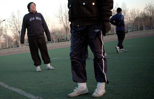 A group of men warm up for a game of football wearing Feiyue brand shoes at a field in Beijing.