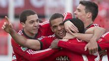 Toronto FC 's Darel Russell, second left, celebrates with teammates after scoring his team's late game tying goal against FC Dallas during second half MLS action in Toronto on Saturday April 6, 2013. (The Canadian Press)