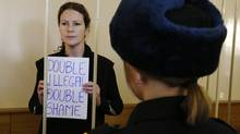 Greenpeace activist Ana Paula Alminhana Maciel from Brazil, one of the 30 people arrested over a Greenpeace protest at the Prirazlomnaya oil rig, holds a sign as she stands in a defendants' cage during a court session in St. Petersburg, November 18, 2013. (ALEXANDER DEMIANCHUK/REUTERS)