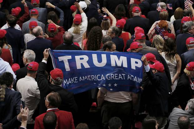 Trump supporters carry a banner at the convention on Thursday.