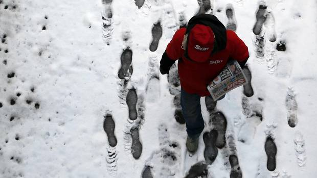"A newspaper seller walks in the snow in central London Jan. 21, 2013. A wintry burst of weather hit businesses and travellers across Britain for a fourth day on Monday, threatening an unprecedented ""triple-dip"" recession that could knock the government's economic plans further off track. (STEFAN WERMUTH/REUTERS)"