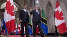 Prime Minister Stephen Harper gestures for President Jakaya Kikwete of the United Republic of Tanzania as they make their way to a joint news conference on Parliament Hill in Ottawa, Oct. 4, 2012. (Adrian Wyld/THE CANADIAN PRESS)