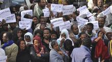 Ethiopians carry posters in Amharic reading 'Meles We Love You' as the body of the late prime minister Meles Zenawi arrived in Addis Ababa, the nation's capital, on Wednesday. (Elias Asmare/Associated Press)