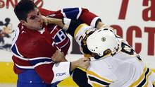 Montreal Canadiens Gregory Stewart, left, fights with Boston Bruin Guillaume Lefebvre during the first period of their NHL preseason hockey action in Montreal, September 24, 2009. (CHRISTINNE MUSCHI)