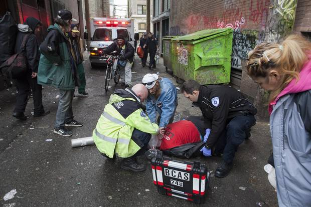 First responders help an overdose victim in a Downtown Eastside alley.