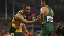 South Africa's Oscar Pistorius (L) congratulates Brazil's Alan Oliveira after Oliveira won the men's 200m T44 classification event at the Olympic Stadium during the London 2012 Paralympic Games September 2, 2012. This classification is for athletes with an impairment that affects their arms or legs, including amputees. (OLIVIA HARRIS/Reuters)