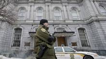 A Sûreté du Québec officer stands outside City Hall in Montreal, Tuesday, Februray 19, 2013, during a raid by officers on the premises. (Graham Hughes/THE CANADIAN PRESS)