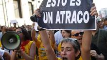 "A civil servant shout slogans during a protest against government austerity measures in front of the Treasury and Public Administration Ministry in Madrid on July 17. The poster reads, ""This is a robbery."" (JUAN MEDINA/REUTERS)"