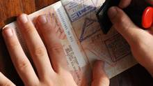 Immigration control stamping a passport. Walter Wolf is a Slovenian-Croatian-German-Canadian (Taolmor/Thinkstock)