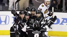 Los Angeles Kings' Jeff Carter (77), Tyler Toffoli (73), Jake Muzzin (6), Dustin Brown (23) and Drew Doughty (8) celebrate a goal by Muzzin as Chicago Blackhawks' Jonathan Toews (19) skates behind them during the first period of Game 4 of the Western Conference finals of the NHL hockey Stanley Cup playoffs on Monday, May 26, 2014, in Los Angeles. (Jae C. Hong/AP)