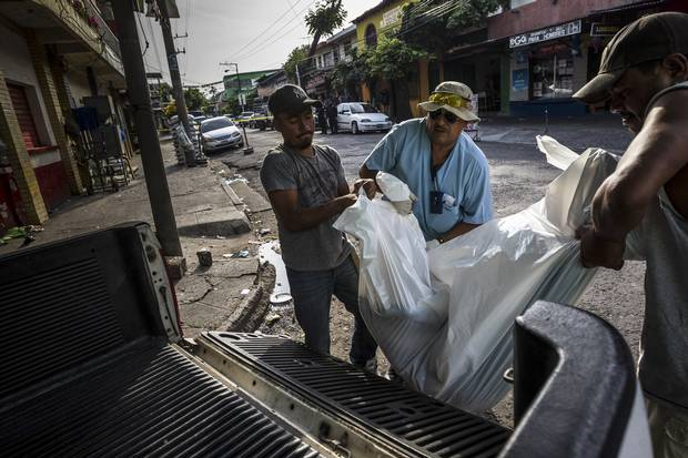 A team from the medical examiner's office take a body to the morgue in San Salvador, El Salvador, May 29, 2015.