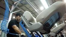 An employee works on a car seat assembly line at a Johnson Controls operation in Bejiing. (NG HAN GUAN/AP)
