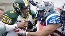Edmonton Eskimos' quarterback Kerry Joseph (5) is sacked by Montreal Alouettes' Luc Mullinder (93) during second half CFL football action against the Montreal Alouettes in Montreal, Sunday, October 28, 2012. (Graham Hughes/THE CANADIAN PRESS)