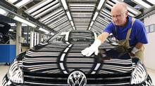 In this Nov. 9, 2012 worker Michael Keil checks a Golf VII car during a press tour at the plant of the German car manufacturer Volkswagen AG (VW) in Zwickau, central Germany. (Jens Meyer/AP)