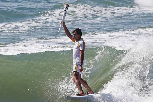 Brazilian surfer Carlos Burle holding the Olympic torch as it visits Porto de Galinhas, Ipojuca, in the Brazilian norteastern state of Pernambuco.