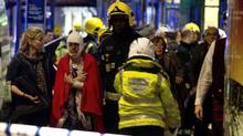 A woman stands bandaged and wearing a blanket given by emergency services following an incident at the Apollo Theatre, in London's Shaftesbury Avenue, Thursday evening, Dec. 19, 2013, during a performance at the height of the Christmas season.