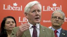 With his wife Arlene Perly Rae and Montreal MP Marc Garneau looking on, newly-appointed interim Liberal Leader Bob Rae speaks to reporters in Ottawa on May 25, 2011. (Adrian Wyld/THE CANADIAN PRESS)