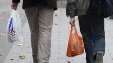 Shoppers hold Tesco and Sainsbury's supermarket carrier bags in London October 5, 2011. (LUKE MACGREGOR/LUKE MACGREGOR/Reuters)