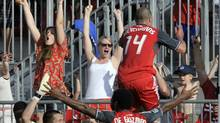 Toronto FC's Danny Koevermans (14) celebrates his goal with fans as teammate Julian de Guzman (6) during the second half of their MLS soccer match in Toronto May 26, 2012. (Reuters)
