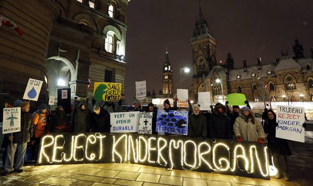 People gather to protest against the proposed Kinder Morgan pipeline outside Prime Minister Justin Trudeau's office in Ottawa.