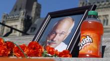 On the steps of Parliament Hill a photograph of Jack Layton is surrounded with flowers, a bottle of Orange Crush and other messages to commemorate the first anniversary of Layton's death during a gathering on Parliament Hill, in Ottawa, Aug. 22, 2012. (Fred Chartrand/The Canadian Press)