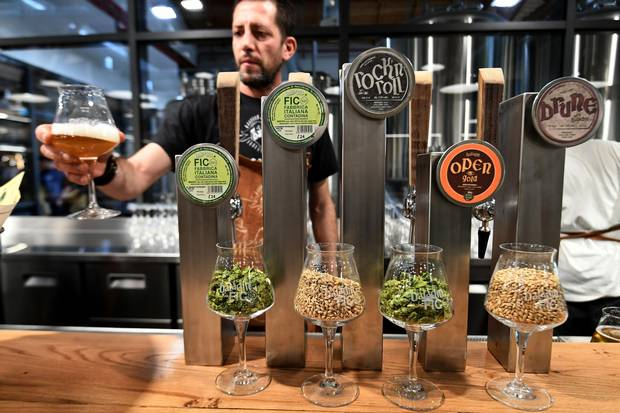 A man offers a glass of artisanal beer at a stand during a press tour at FICO Eataly World agri-food park in Bologna on November 9, 2017. FICO Eataly World, said to be the world's biggest agri-food park, will open to the public on November 15, 2017.