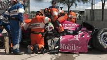 Safety team members work to remove Dario Franchitti from his car after a crash during the second IndyCar Grand Prix of Houston auto race, Sunday, Oct. 6, 2013, in Houston. (Juan DeLeon/AP Photo)